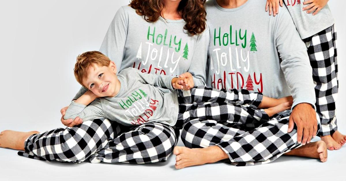 family wearing holiday buffalo check fleece pajama pants and matching shirts