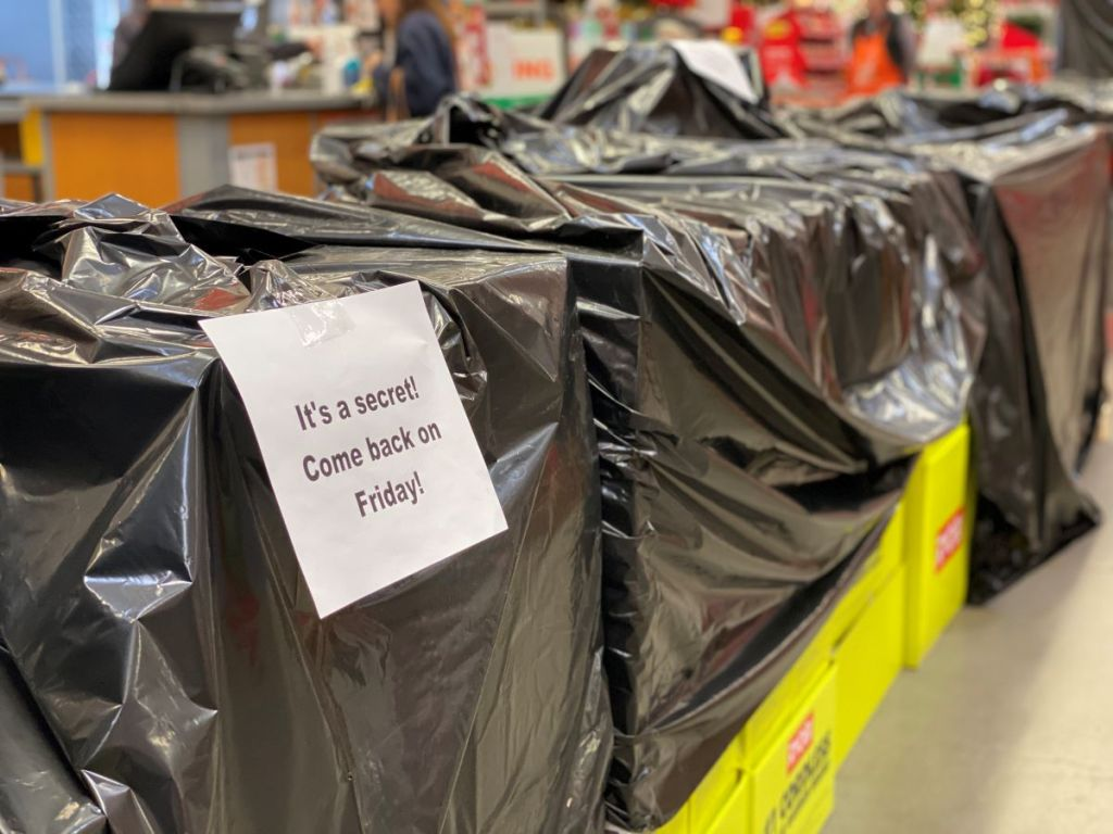 kotak-kotak yang dilapisi terpal hitam dan tanda yang bertuliskan untuk memeriksa kembali Black Friday