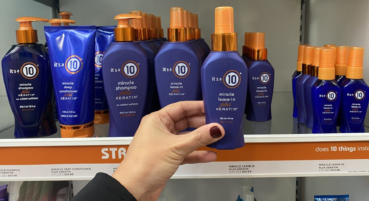 hand holding a bottle of hair care in store in front of shelf