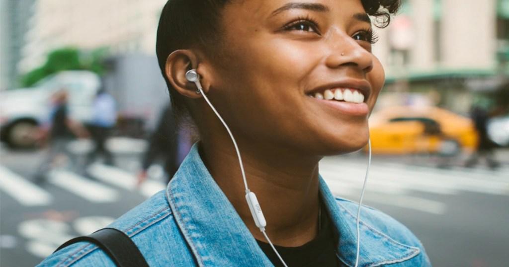 A lady outside walking in town wearing JBL in ear headphones, smiling