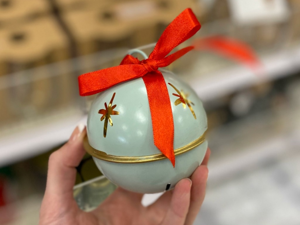 Green Jingle Bell ornament in hand in Target