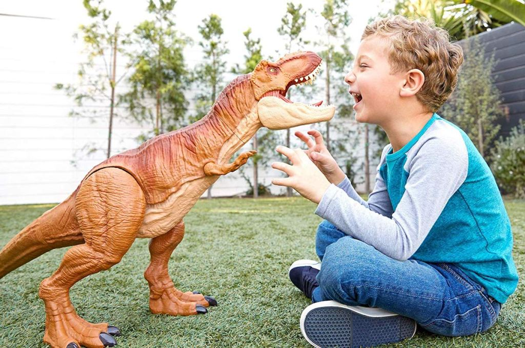 boy playing with Jurassic World Super Colossal Tyrannosaurus Rex in backyard on grass