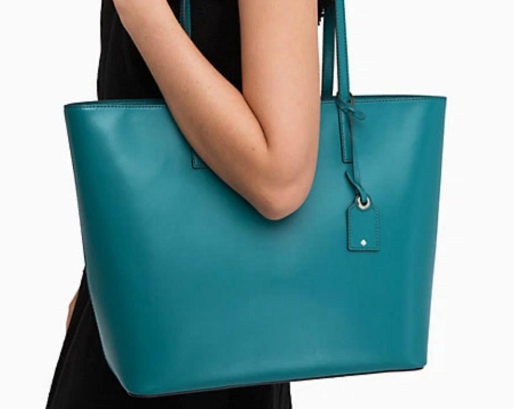 Woman wearing a teal Kate Spade tote bag