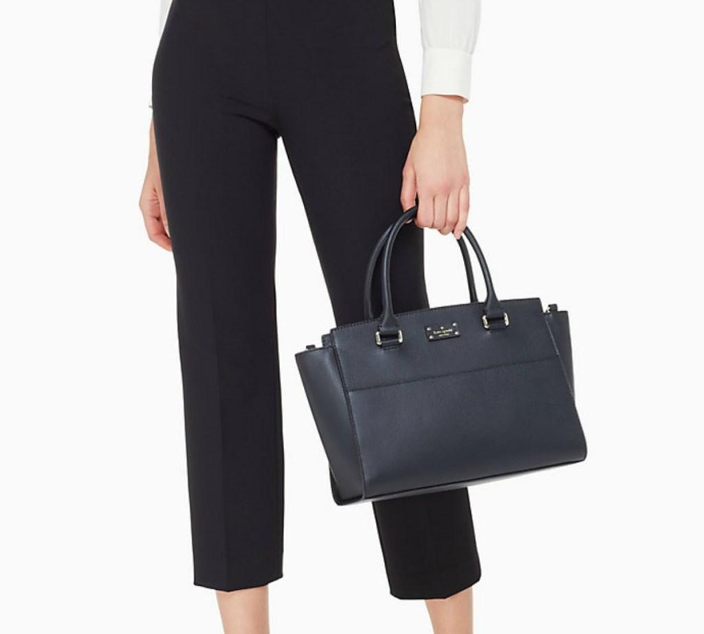 woman in black capri pants holding a black purse