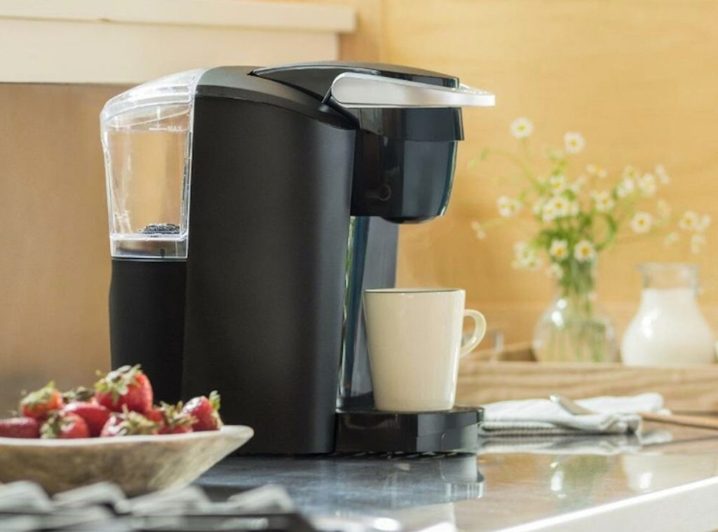 keurig sitting on kitchen counter with mug and bowl of strawberries