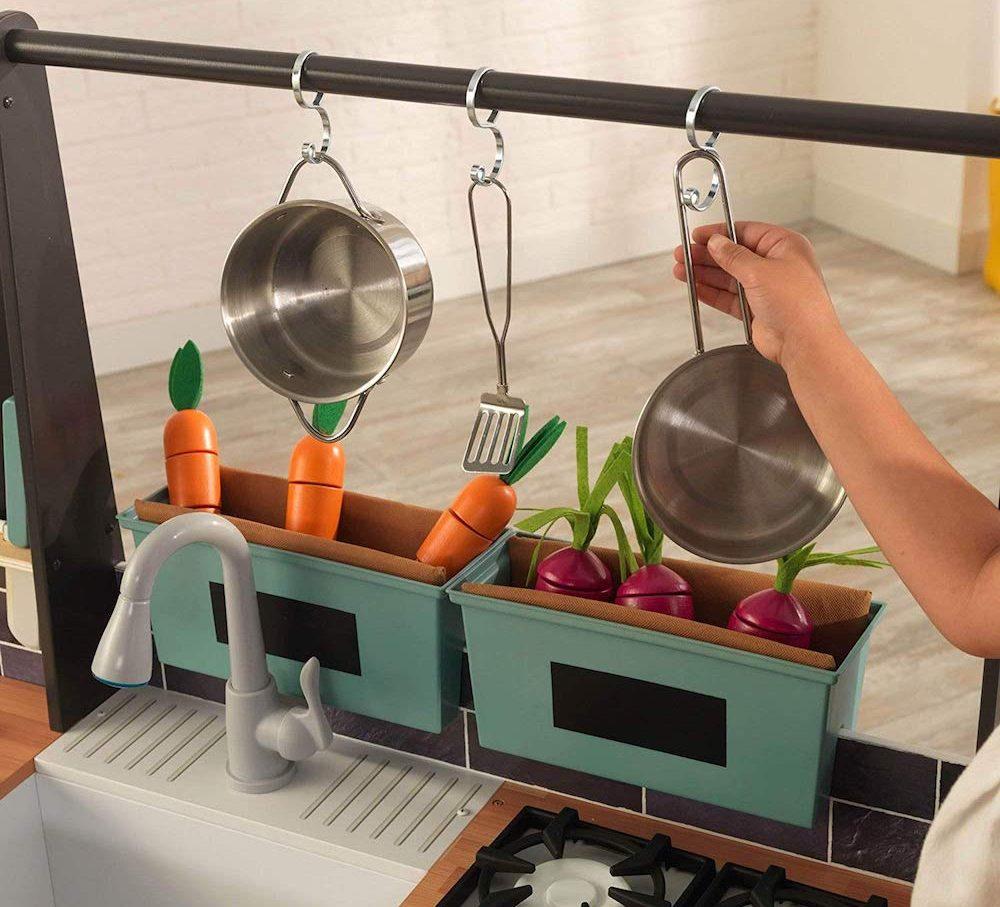 kid grabbing pan from KidKraft Farm to Table Kitchen Set