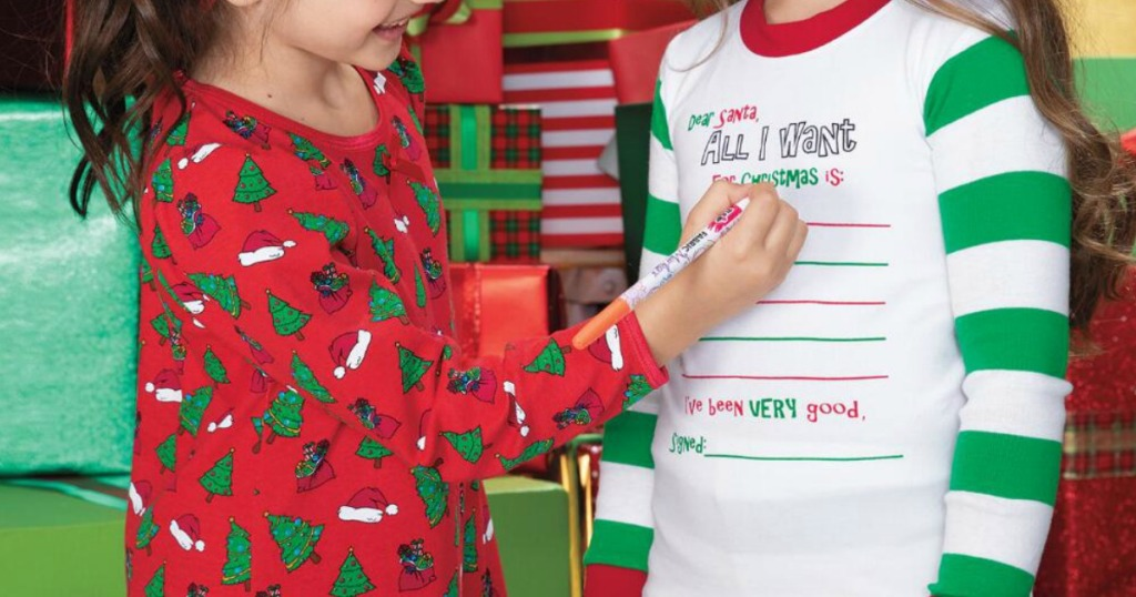 Two kids wearing Chasing Fireflies holiday pajamas