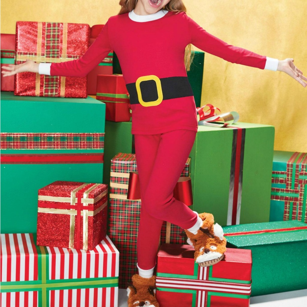 Girl wearing Santa-themed pajamas standing on presents