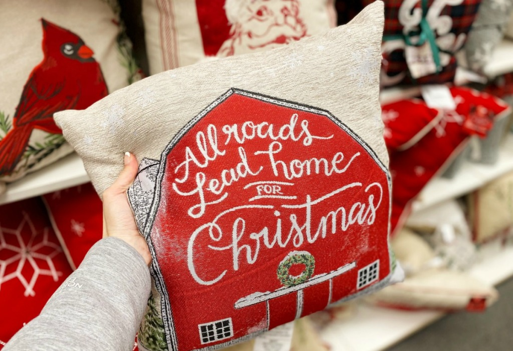 Barn-themed holiday throw pillow in hand in-store