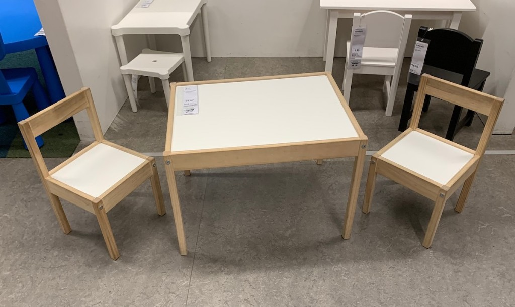 white and natural wood colored table and two chairs sitting on cement floor