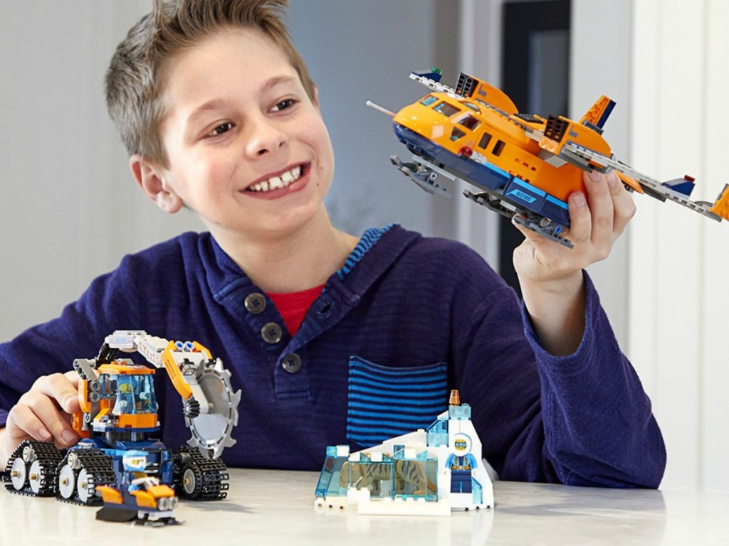 Boy playing with a LEGO City set with a plane