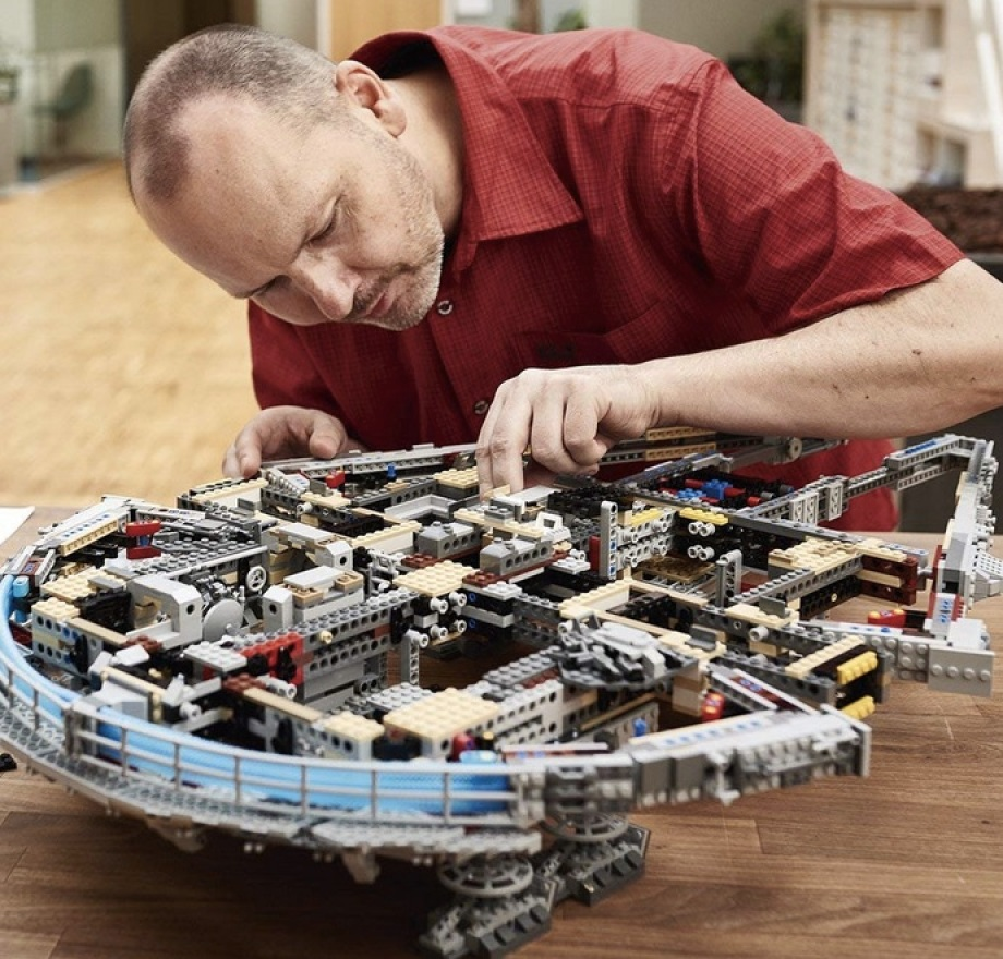 Man building LEGO Star Wars Ultimate Millennium Falcon Expert Building Kit and Starship Model