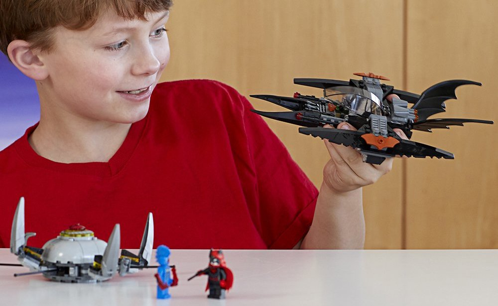 boy playing with LEGO Super Heroes Batman- Brother Eye Takedown Set