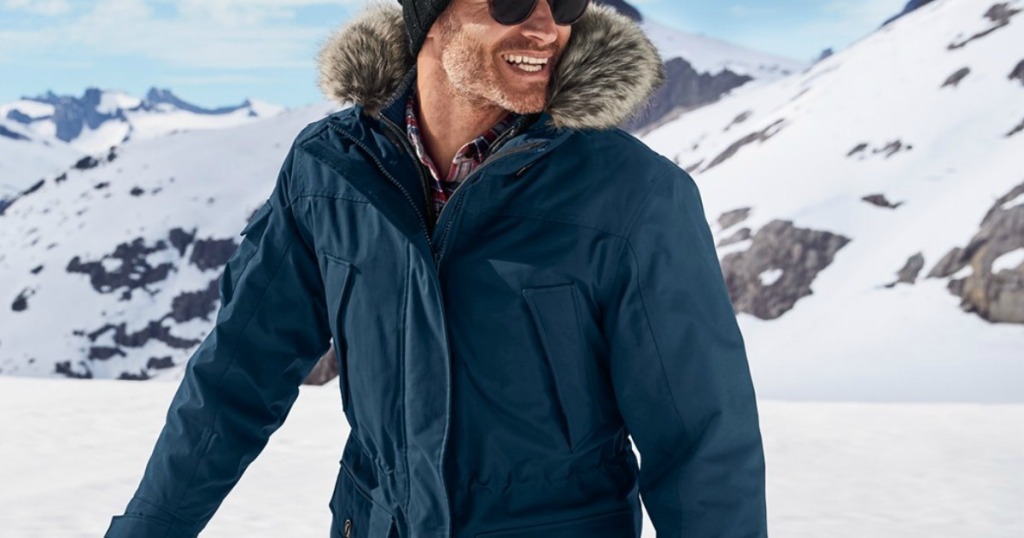 Man wearing a teal winter parka in the mountains