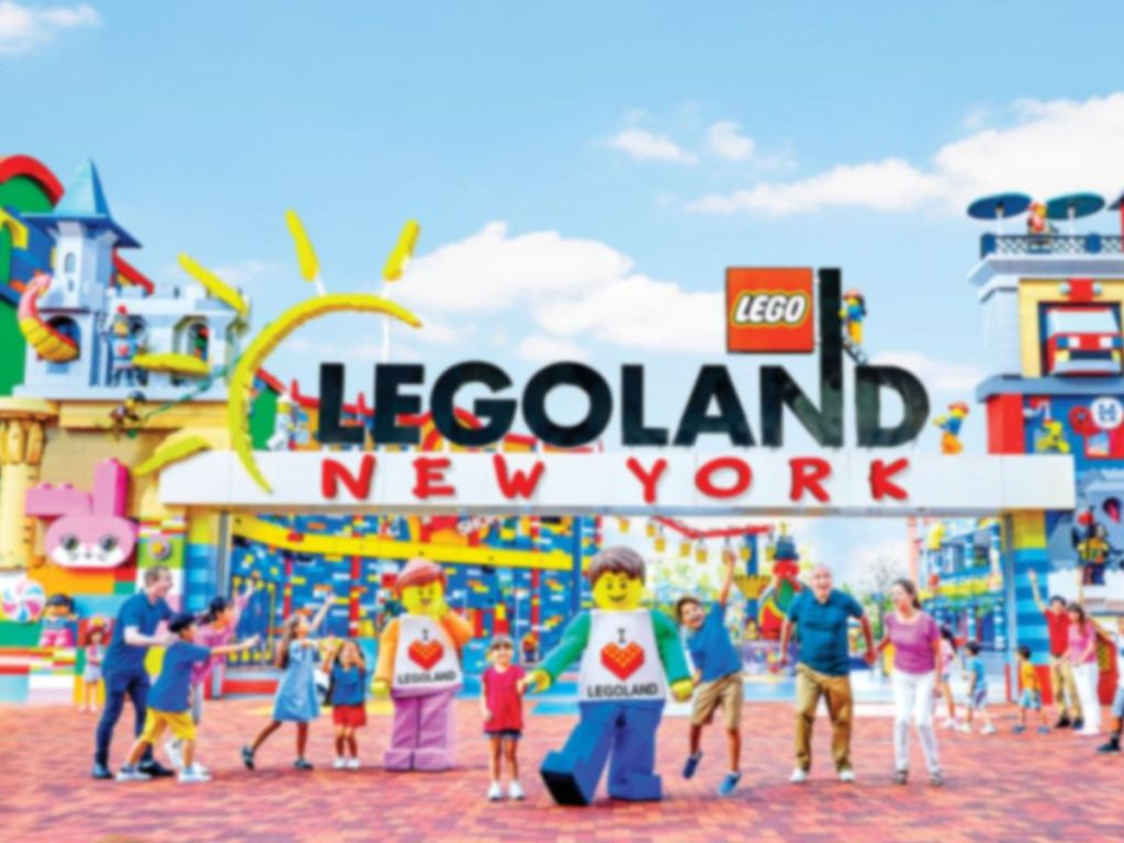 Legoland new york sign with people and characters in front