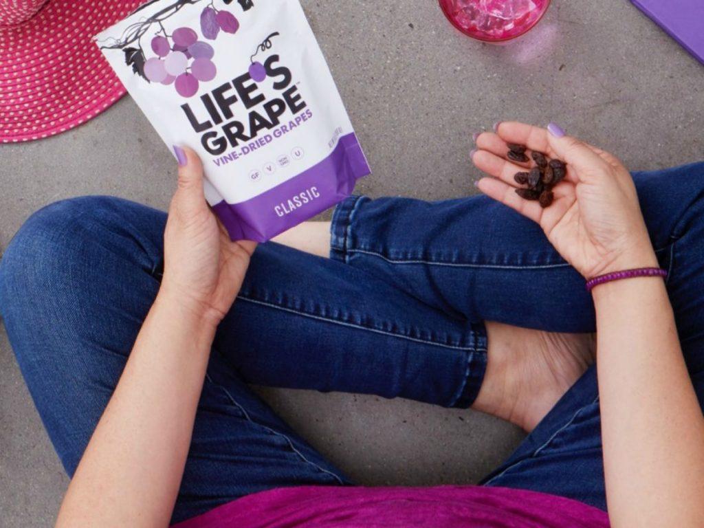 Woman holding bag of Life's grape