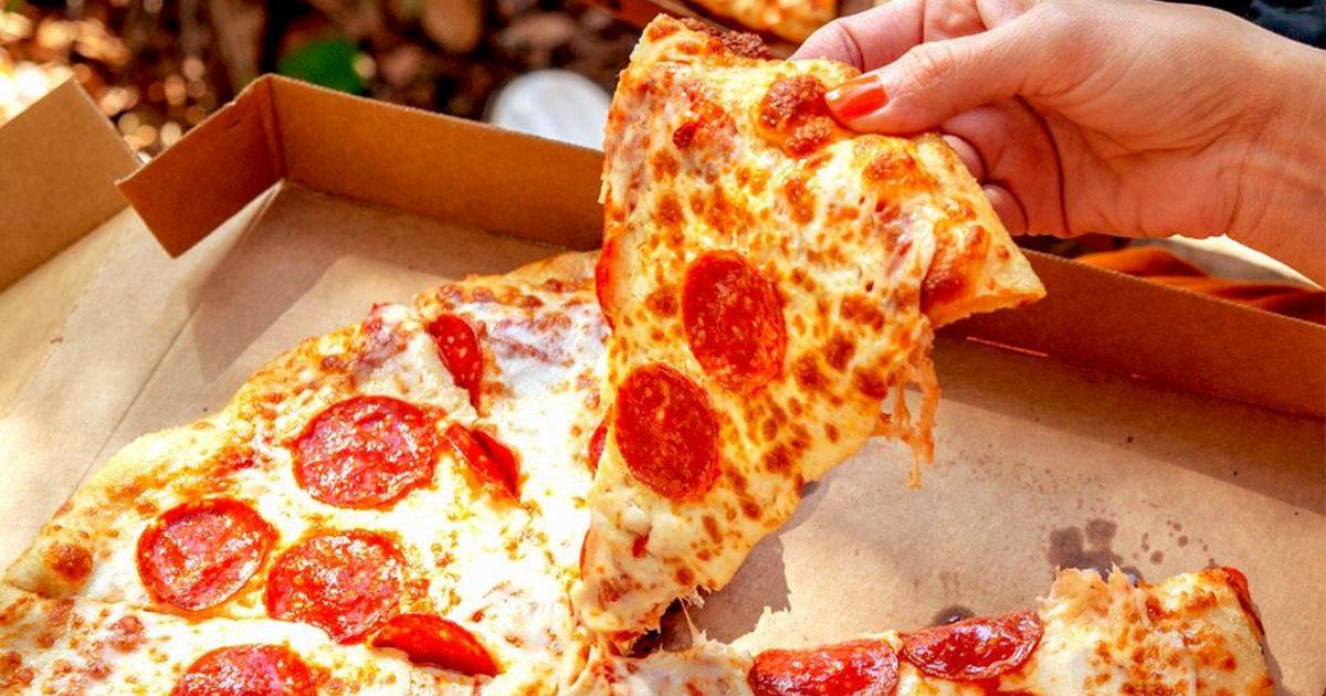 hand holding slice of little caesar pepperoni pizza