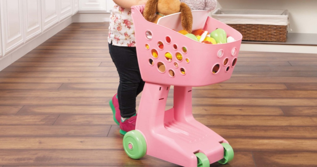 kid playing with pink little tikes lil shopper