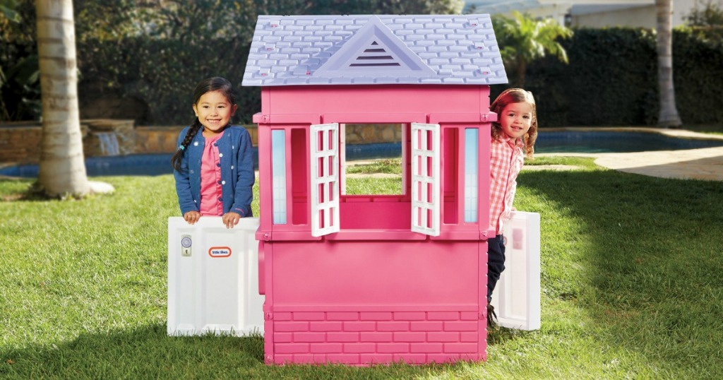 two girls playing in a Little Tikes Princess Cottage Playhouse