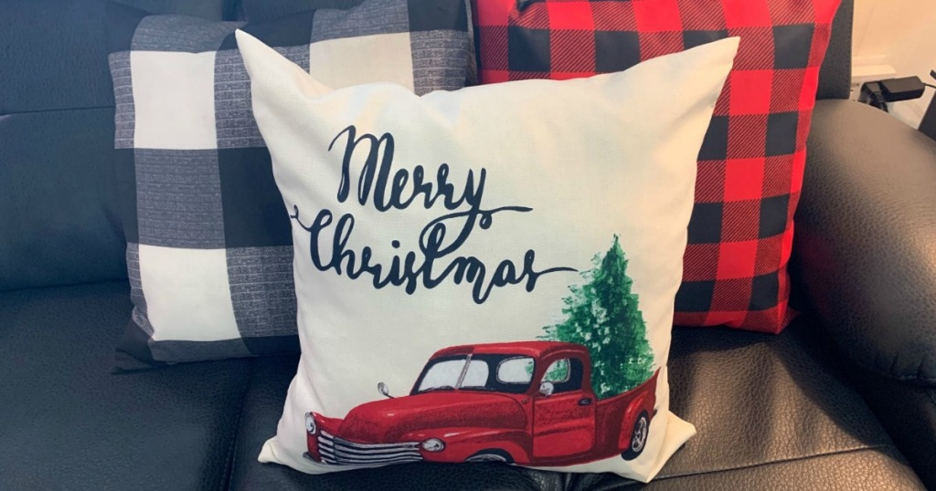 holiday pillow with red truck, pine tree and Merry Christmas written on it