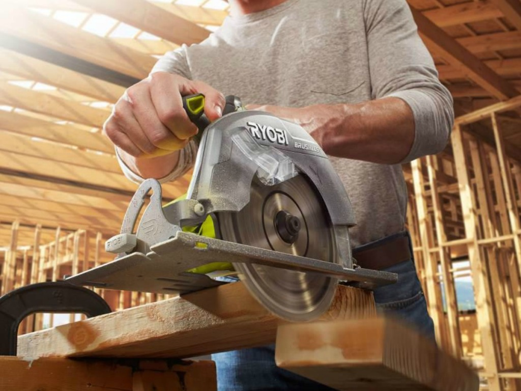 Man using a Ryobi Power Saw on a large piece of wood in a workshop