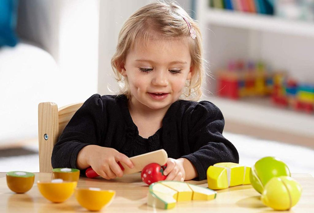 girl playing with Melissa & Doug Cutting Fruit Set