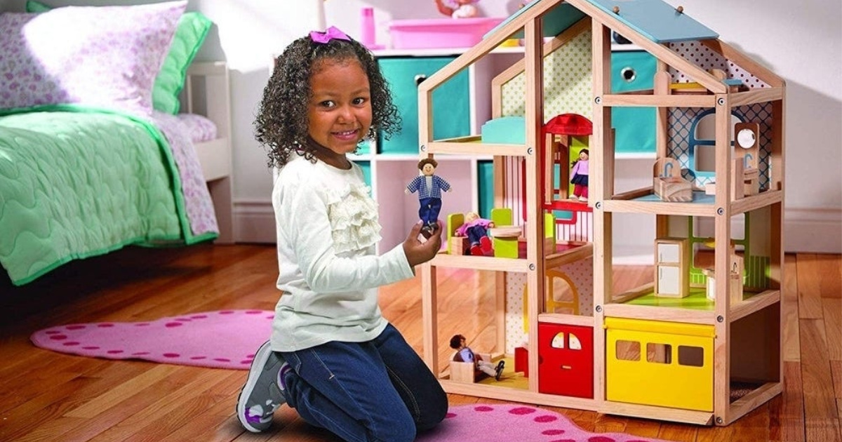 girl playing with melissa and doug dollhouse
