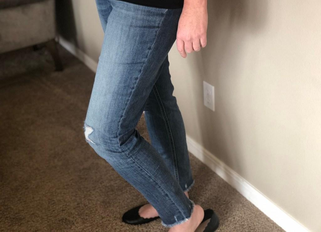 woman's legs wearing medium wash denim