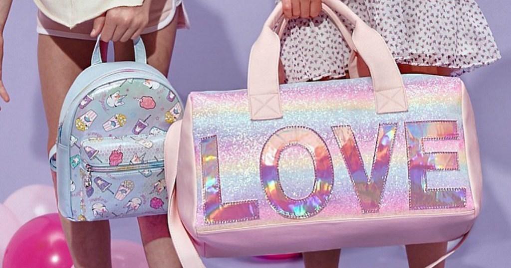 girl holding OMG! LOVE duffel bag