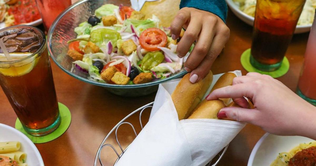 Women taking breadsticks from basket at Olive Garden