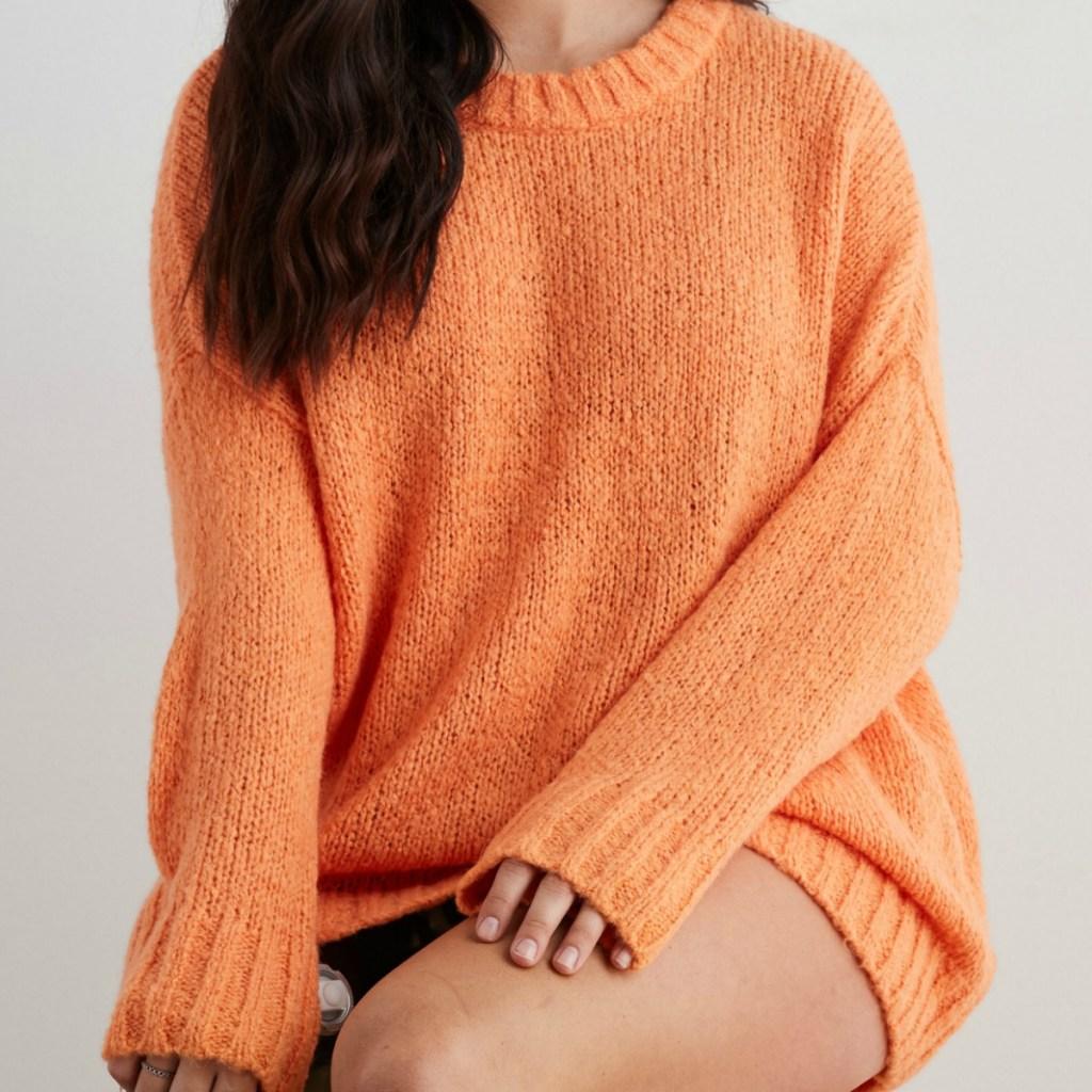 Woman wearing an orange oversized sweater