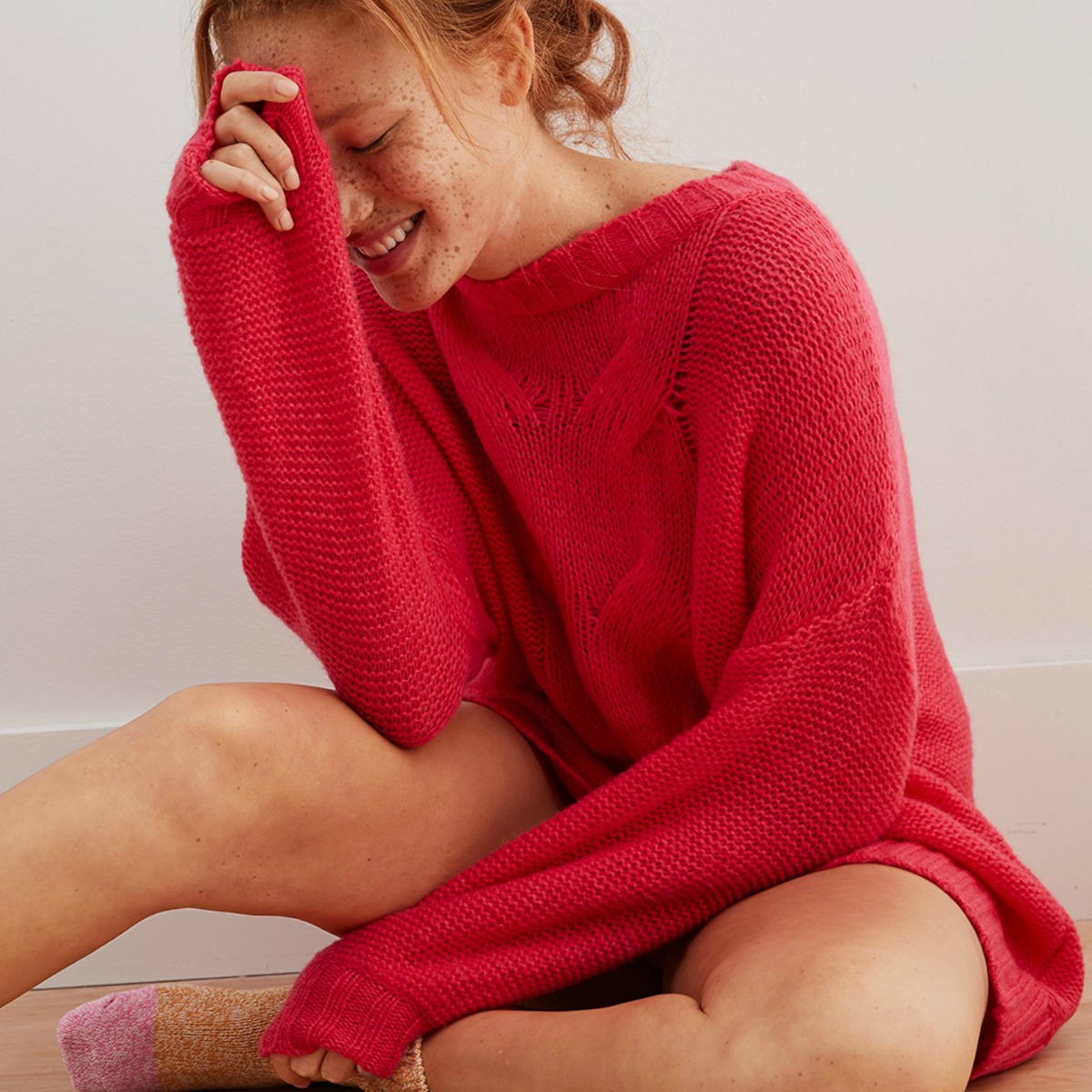 Woman wearing a red oversized cable sweater