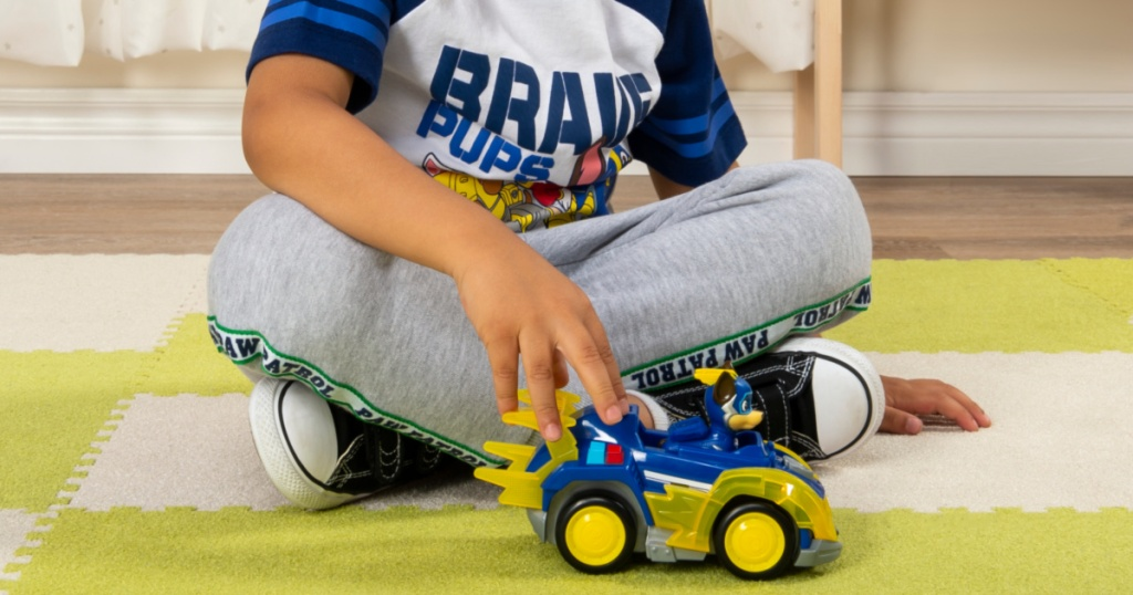boy playing with paw patrol chase deluxe vehicle toy