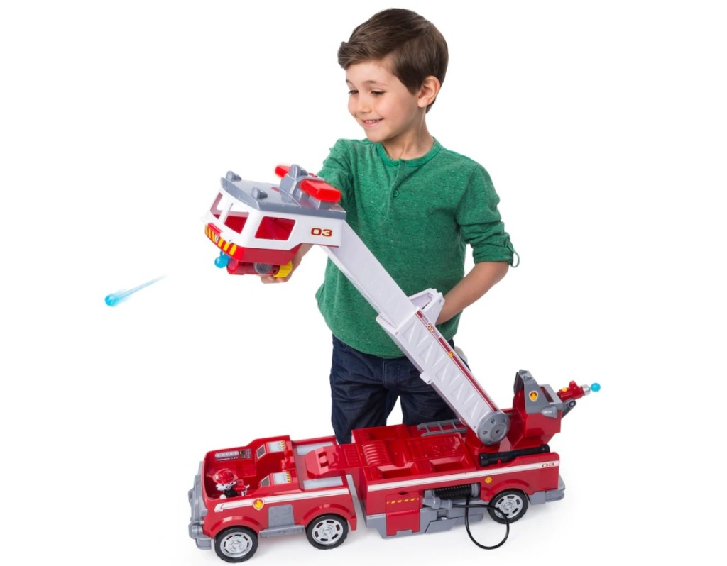 boy playing with Paw Patrol rescue fire truck