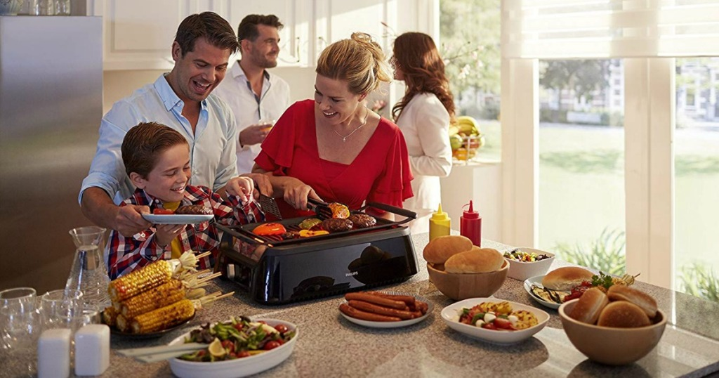 people usig Philips Smoke-less Indoor BBQ Grill on counter surrounded by food