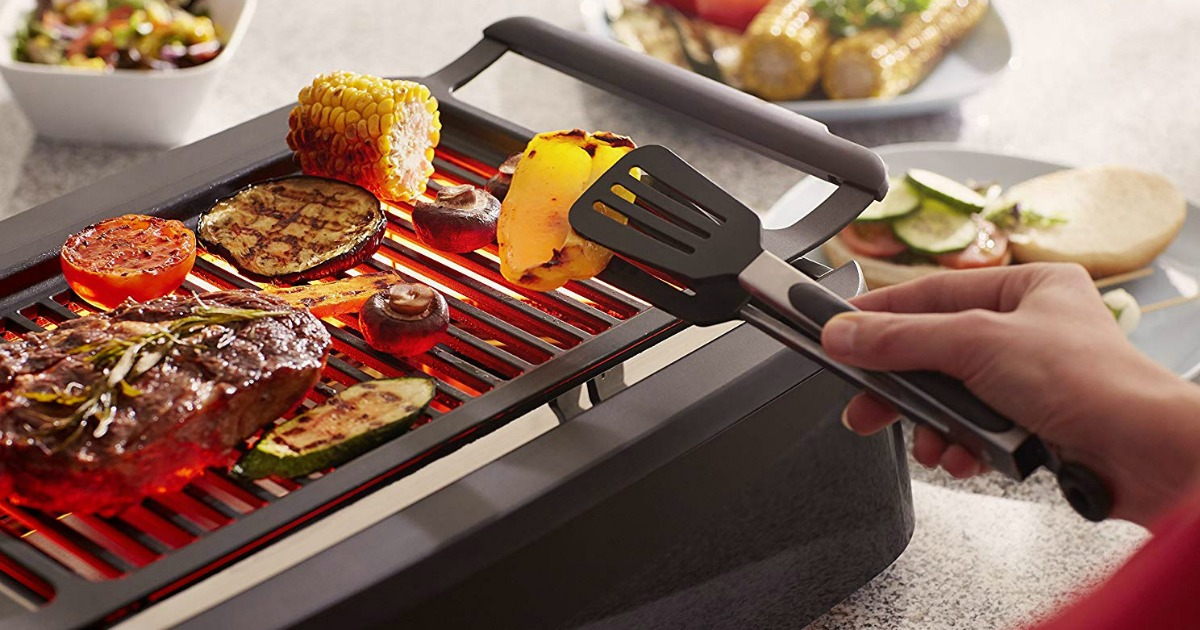 person using tongs to turn vegetables on Philips smokeless grill