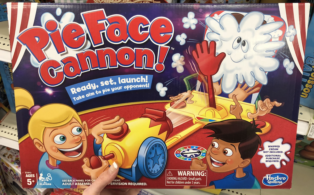 hand holding Pie Face Cannon game box