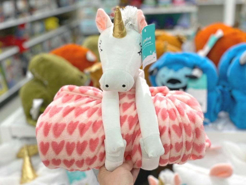 Unicorn plush holding a heart throw blanket