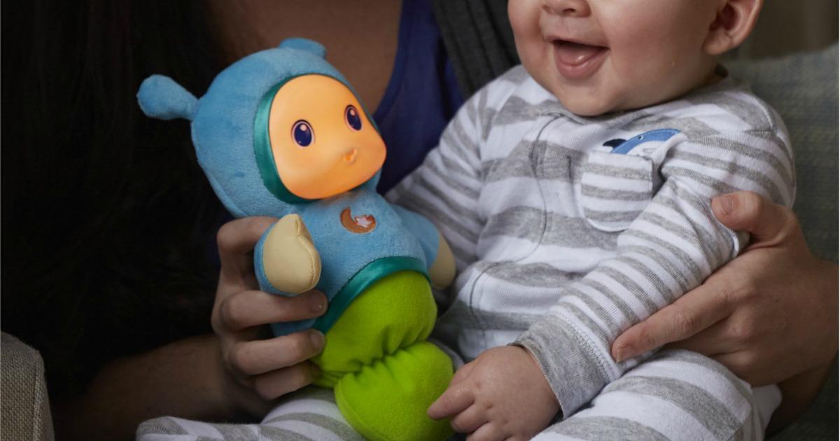 baby holding Playskool Gloworm toy