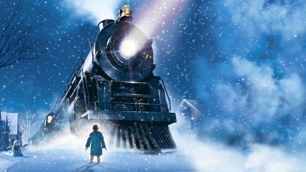 the polar express train outside with boy standing in snow
