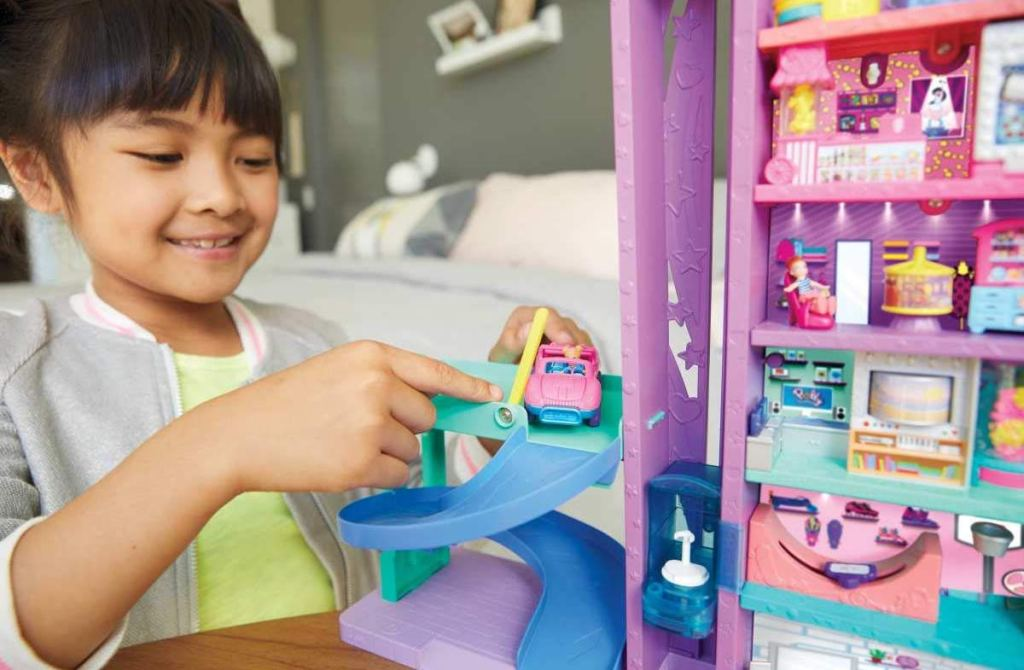 girl playing with Polly Pocket Mega Mall using car on driving ramp