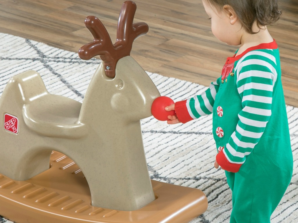 Small child looking at a rocking reindeer toy
