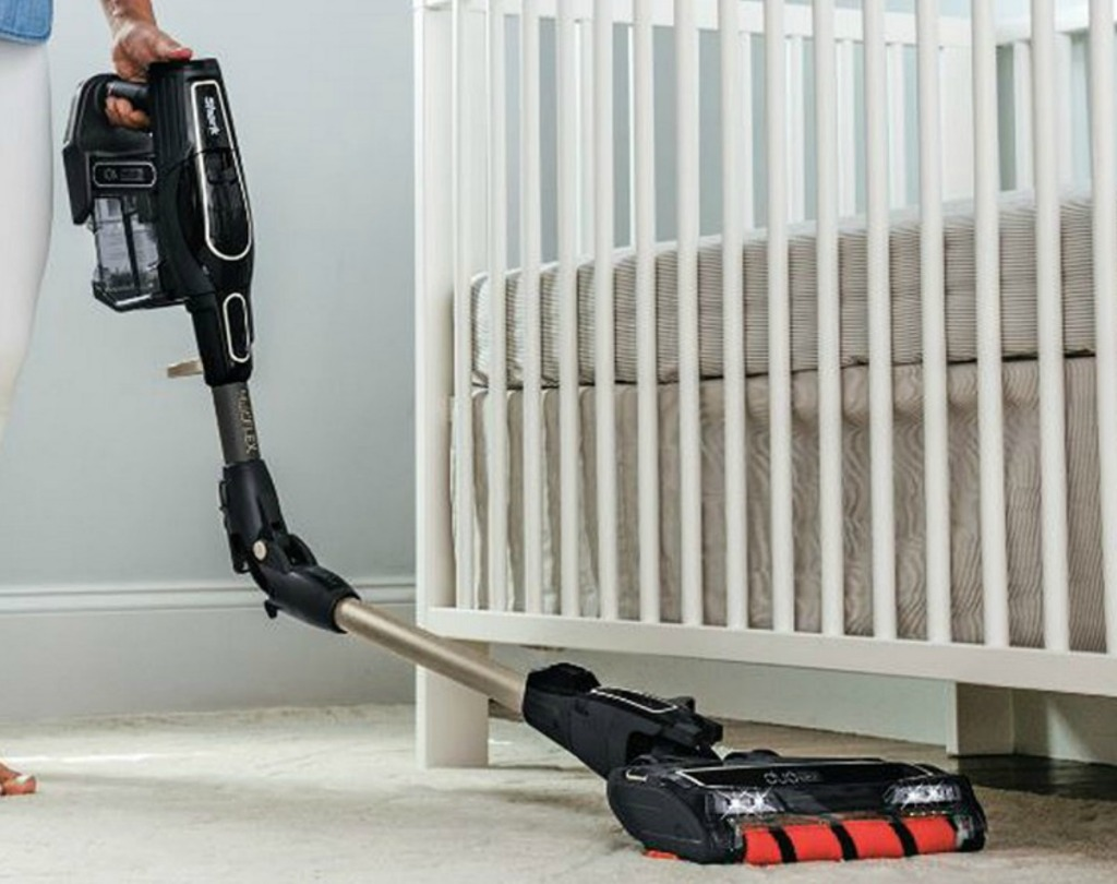 Woman using a Shark Handheld vacuum under a crib in a nursery