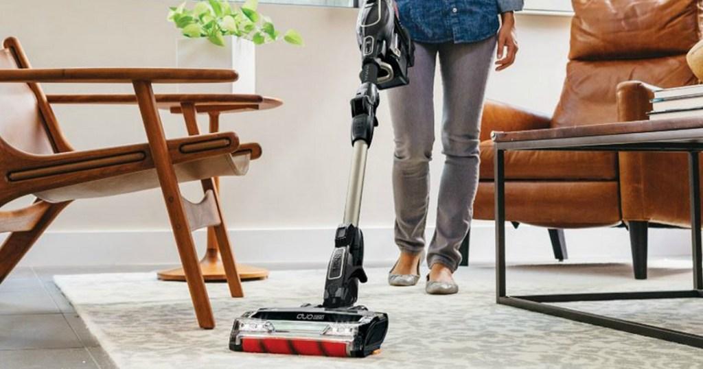 Woman vacuuming using the Shark ION Cord-Free MultiFLEX Vacuum F80 in living room on area rug