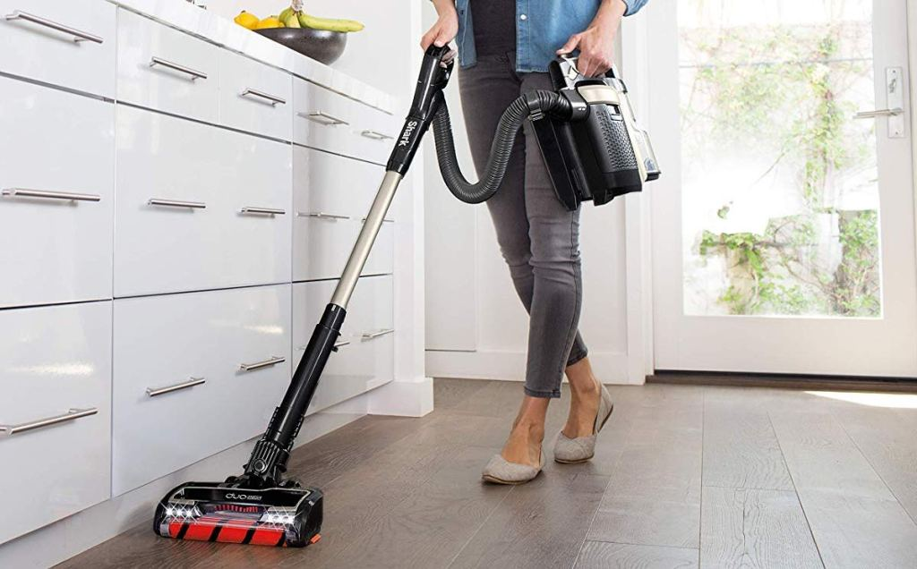 woman cleaning the floor with a vacuum