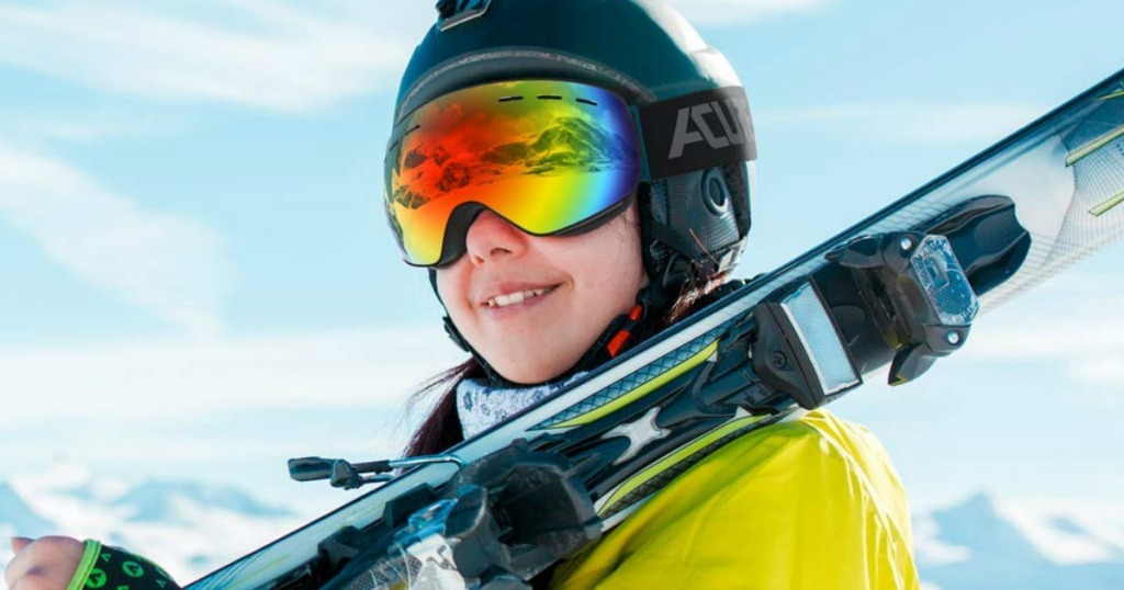 girl wearing ski goggles holding skis