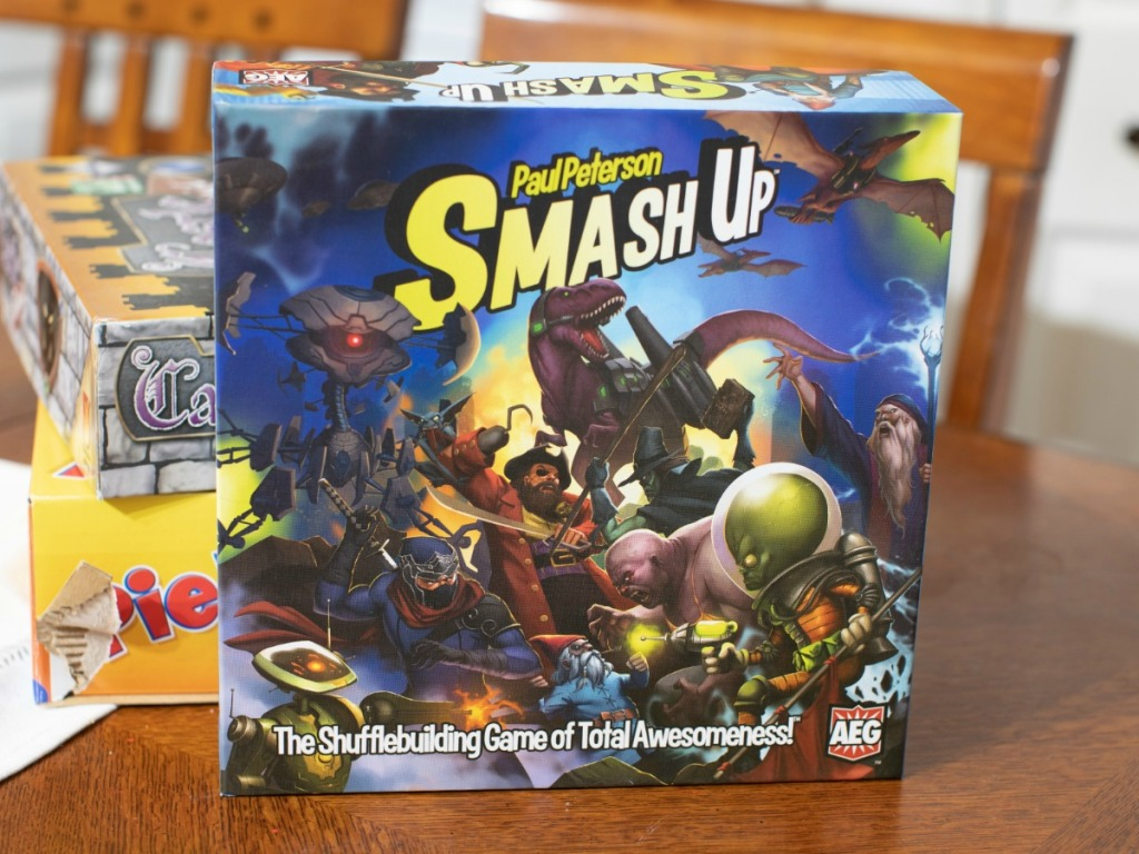 Smash Up Card Game in front of stack of games