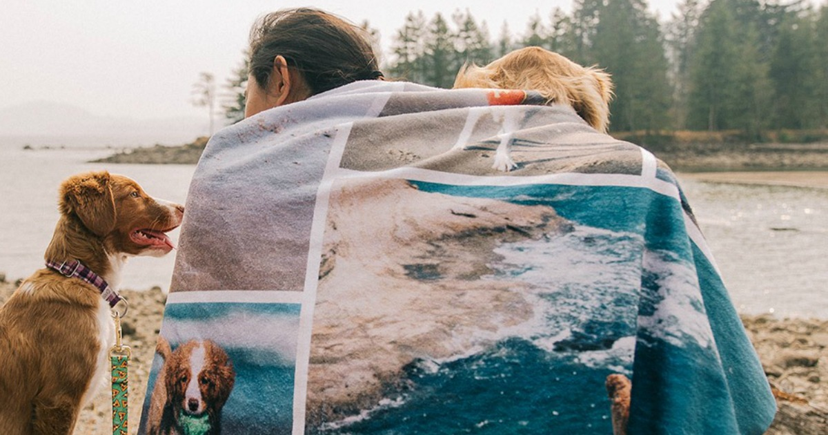 Person with two dogs on the beach wearing a Snapfish Personalized photo blanket