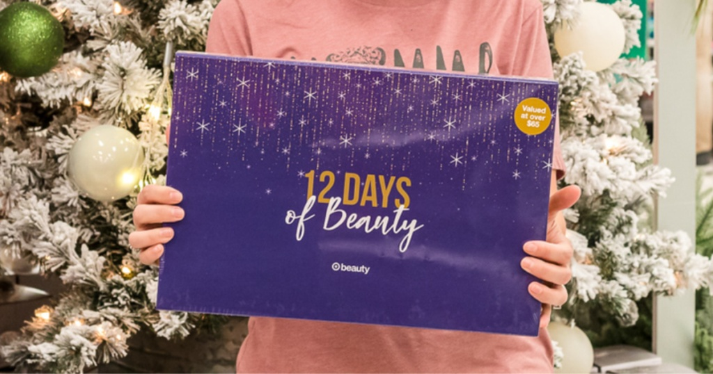 woman wearing a pink shirt holding Target 12 Days of Beauty advent calendar box in front of white christmas tree inside target