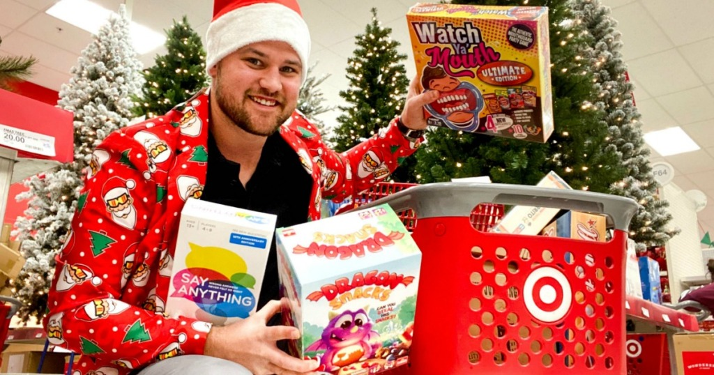 Man shopping in Target with board games near Christmas Trees
